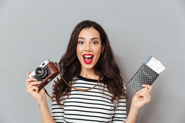 ビンテージカメラを保持している興奮した女性の肖像画