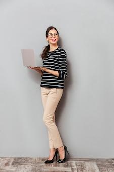 眼鏡で幸せな女性の完全な長さの肖像画