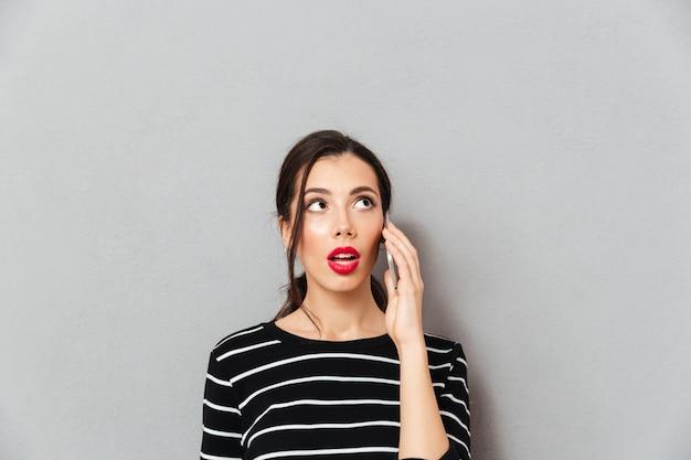 Портрет удивленной женщины разговаривает по мобильному телефону