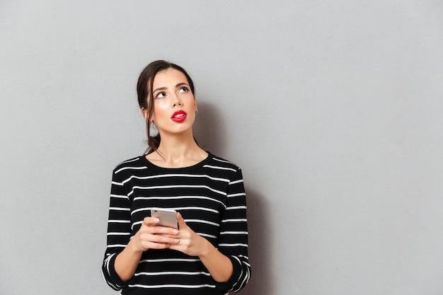 Портрет серьезной женщины, держащей мобильный телефон