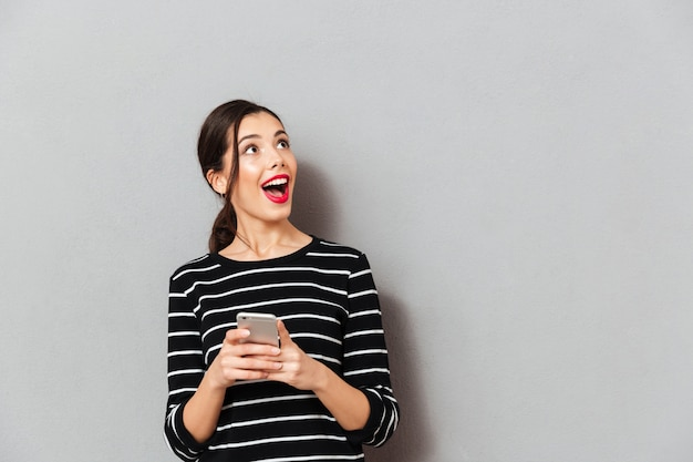 Портрет счастливой женщины, держащей мобильный телефон