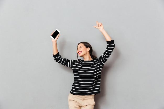 Портрет жизнерадостная женщина, держащая мобильный телефон