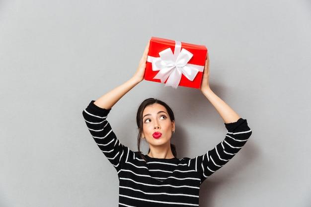 Портрет красивой женщины, держащей подарочную коробку