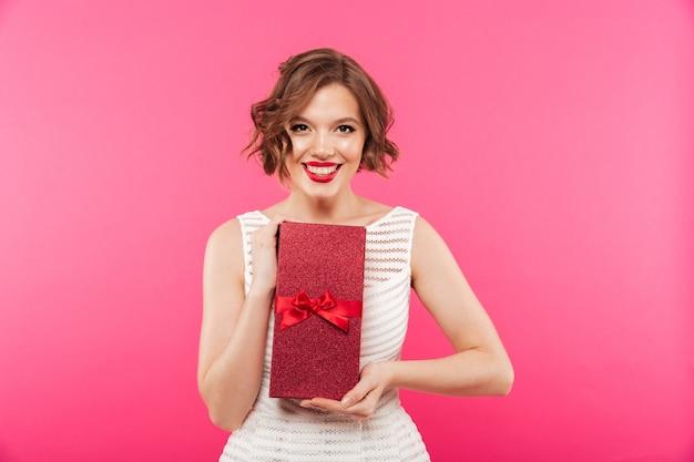 Портрет улыбающейся девушки, одетой в платье с подарком