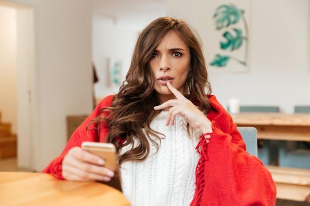 Портрет потрясенной женщины, держащей мобильный телефон