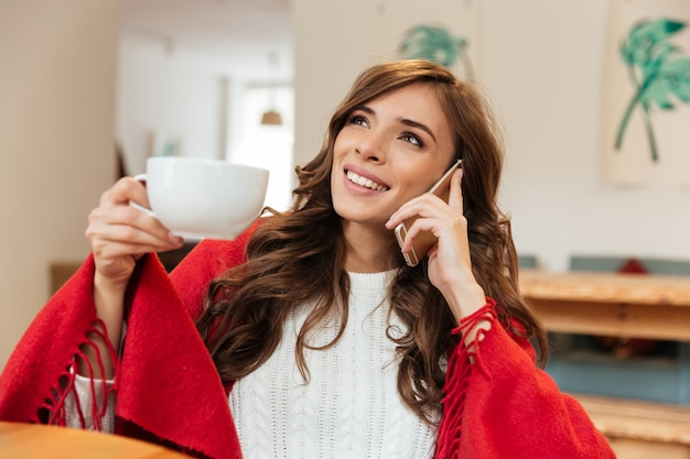Портрет улыбающейся женщины разговаривает по мобильному телефону