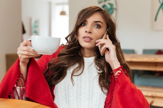 携帯電話で話している驚く女性の肖像画