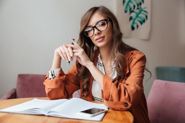 テーブルに座っている自信を持って女性の肖像画