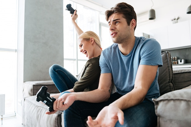 自宅で彼女の男と遊んでいる間勝者ジェスチャーを作るきれいな女性