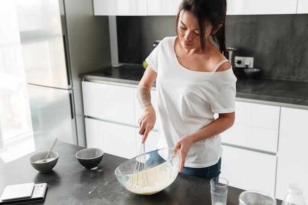 Удивительная молодая леди, стоя на кухне в домашней кухне