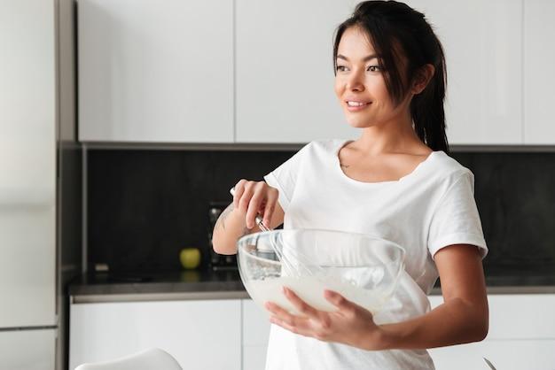 台所に立っている美しい若い女性