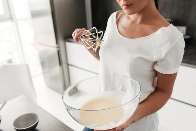 家の台所に立っている素晴らしい若い女性