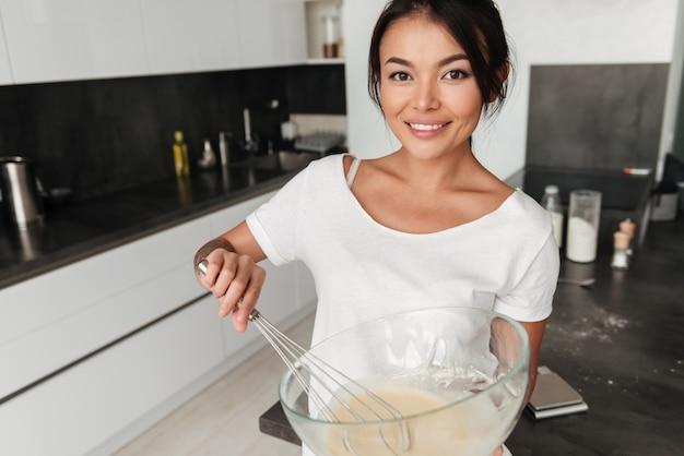 家の台所に立っている笑顔の若い女性