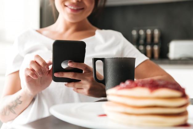 Подрезанное фото жизнерадостной молодой женщины используя мобильный телефон