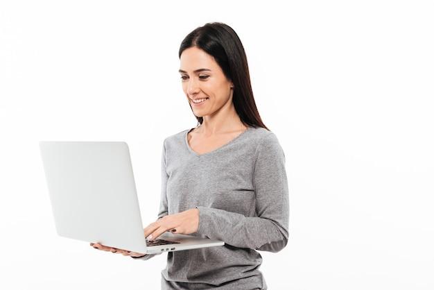 ラップトップコンピューターを使用して若い幸せな女。