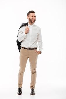 ジャケットを保持している幸せな若い男の完全な長さの肖像画