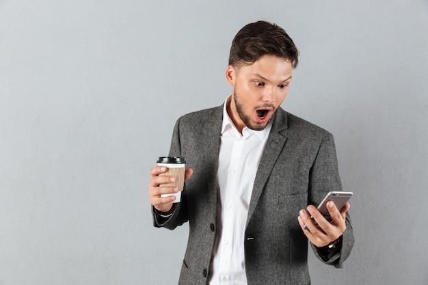 Портрет потрясенного бизнесмена смотря мобильный телефон