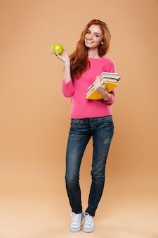 Полная длина портрет улыбающегося довольно рыжая девушка держит книги и яблоко