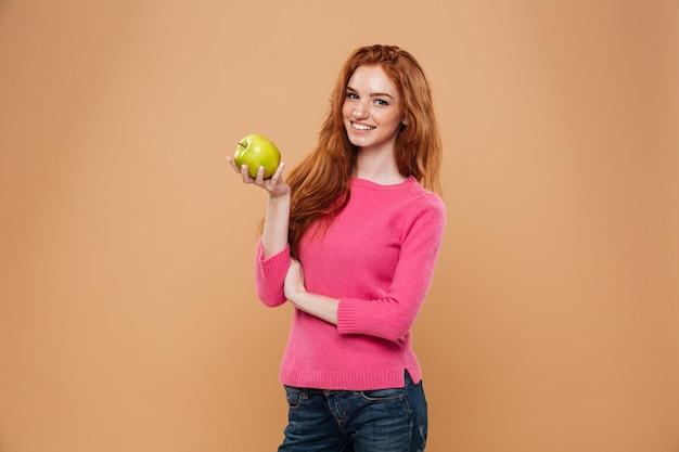 Портрет улыбающегося довольно рыжая девушка держит яблоко