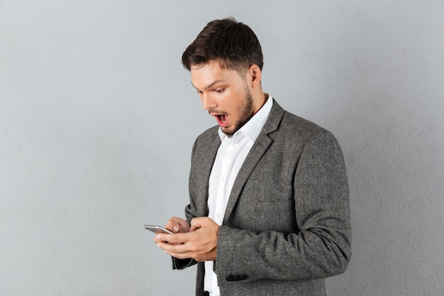 携帯電話を見て驚いた実業家の肖像画