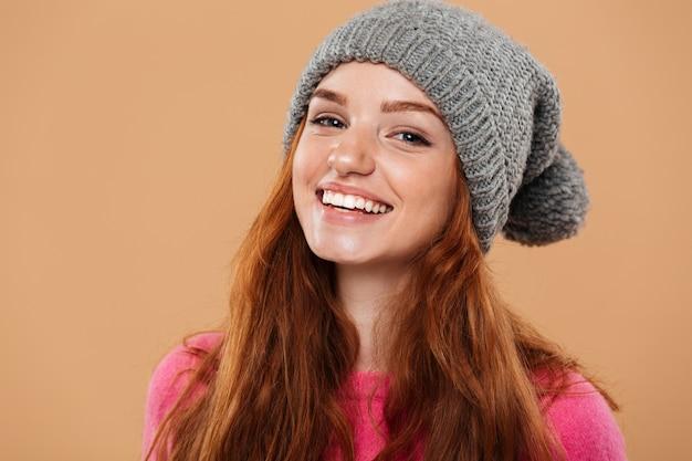 Крупным планом портрет радостного довольно рыжая девушка в зимней шапке