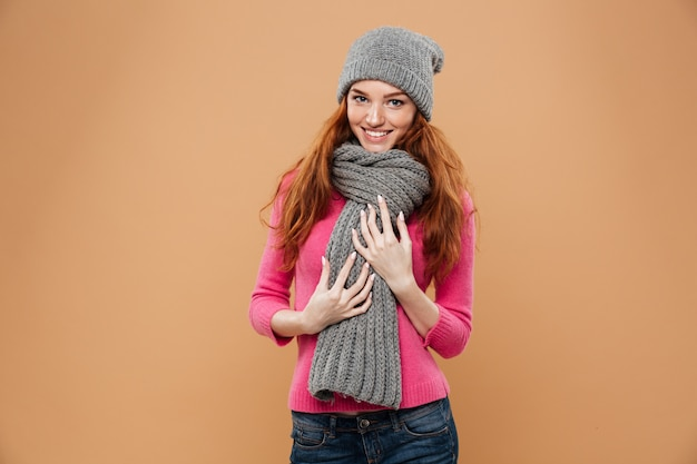 Портрет счастливой довольно рыжая девушка, одетая в зимней шапке