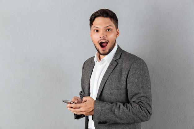 Портрет возбужденного бизнесмена, держащего мобильный телефон