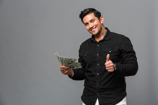 お金を持って親指を示す幸せな男。