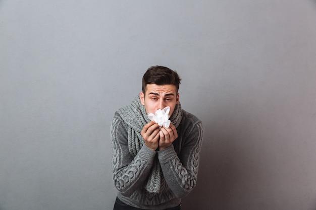 Раздражанный человек болезни нося теплый шарф держа салфетку.