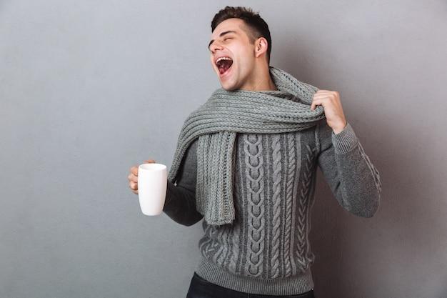 Счастливый больной человек в свитере держит свой лом и чашку чая