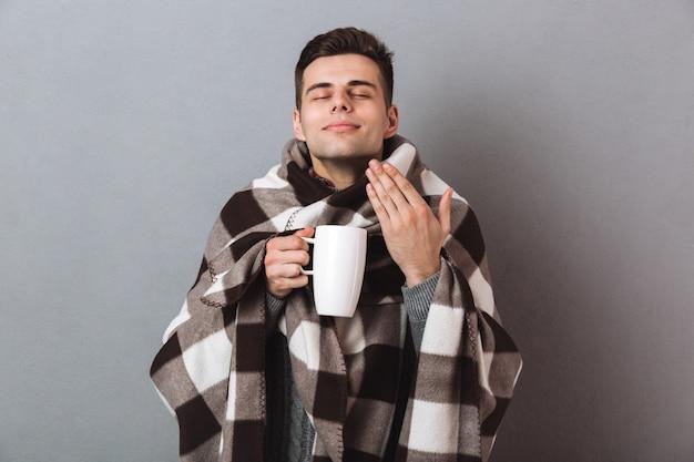 熱いお茶を保持している暖かい格子縞の満足している男はそれをかぐ。