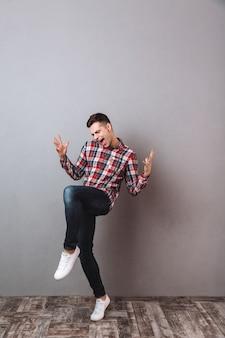 Полнометражное изображение веселого кричащего мужчины в рубашке и джинсах радуются