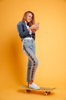 笑顔の若い女の子のスケートボーダーの完全な長さの肖像画
