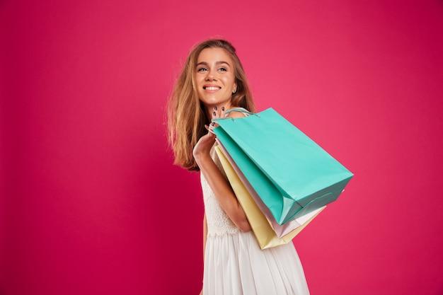 買い物袋を保持している幸せな若い女の子の肖像画
