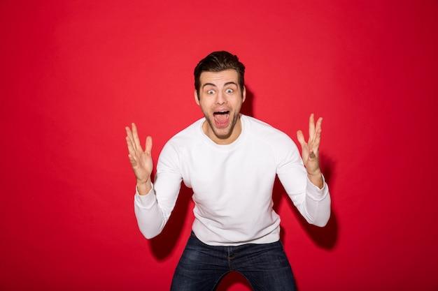 Потрясенный кричащий мужчина в свитере смотрит
