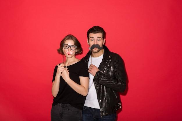 偽の口ひげ、唇、眼鏡でポーズ遊び心のあるパンクカップル