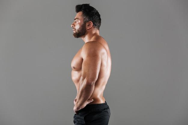 Портрет вида сбоку сосредоточенного сильного мужского культуриста без рубашки