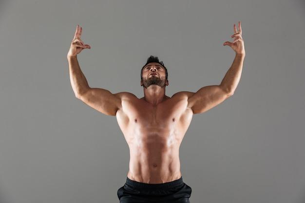 Портрет уверенно сильный без рубашки мужской культурист позирует
