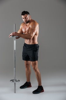 Полная длина портрет мускулистого серьезного без рубашки мужского культуриста
