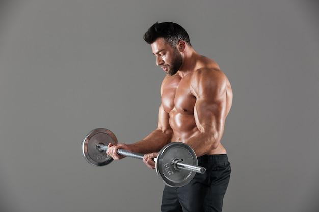 Вид сбоку сосредоточенного сильного мужского культуриста без рубашки