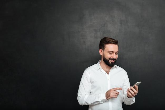テキストメッセージを入力するか、濃い灰色の上のスマートフォンを使用してソーシャルネットワークでフィードをスクロールする白いシャツのコンテンツの笑みを浮かべて男