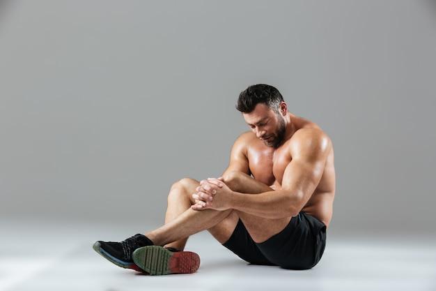 Портрет утомленного сильного без рубашки мужского культуриста отдыхая