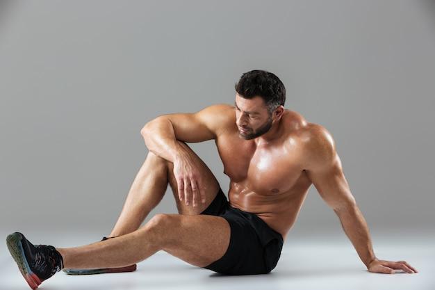 Портрет утомленного сильного без рубашки мужского культуриста ослабляя
