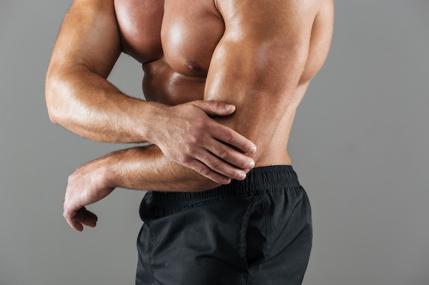 強い筋肉の男性のボディービルダーの肖像画を閉じる