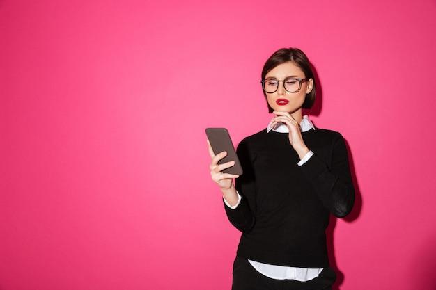 携帯電話を見て物思いにふける魅力的な実業家の肖像画