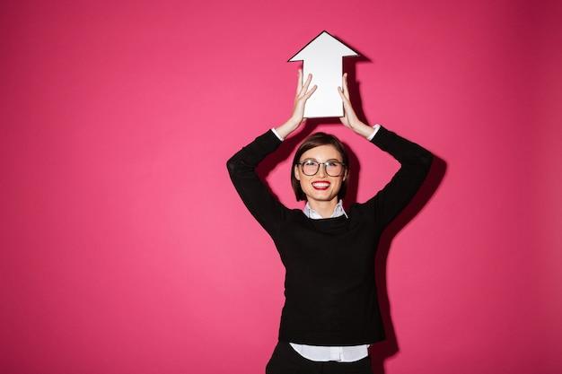 Портрет счастливой молодой коммерсантки держа бумажный знак стрелки