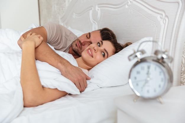 ベッドで一緒に寝ている笑顔の素敵なカップルの側面図