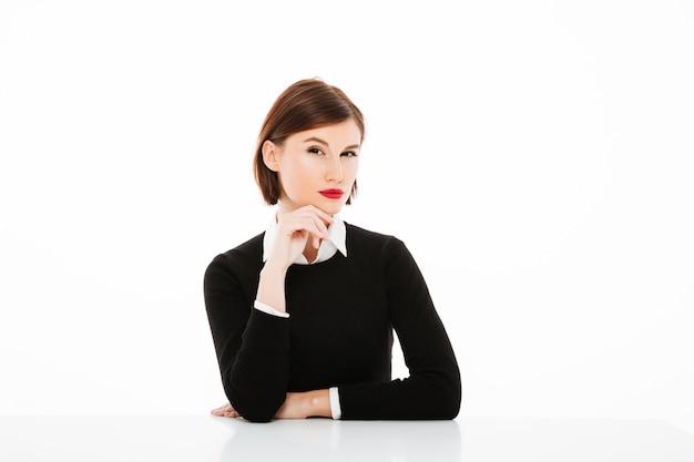 Серьезная молодая бизнес-леди сидя на таблице, концепция собеседования для приема на работу