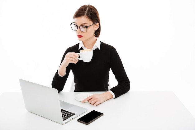ラップトップコンピューターを使用して眼鏡をかけている若いビジネス女性