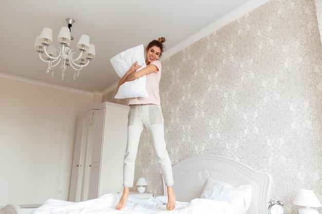ベッドで楽しんで若い女性の完全な長さの画像